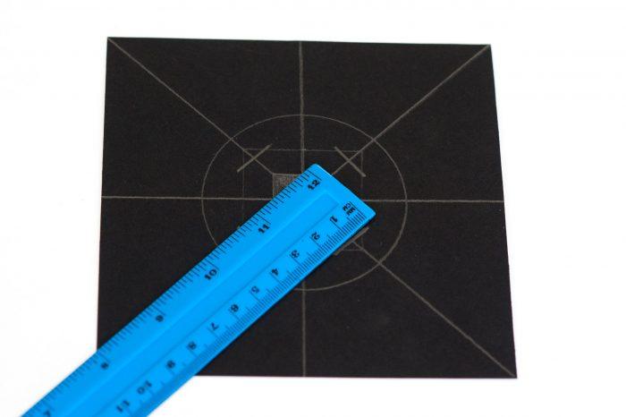 Teken om het middelste vierkantje een groter vierkantje van 4x4cm. Op de hoeken teken je schuine snijlijnen.