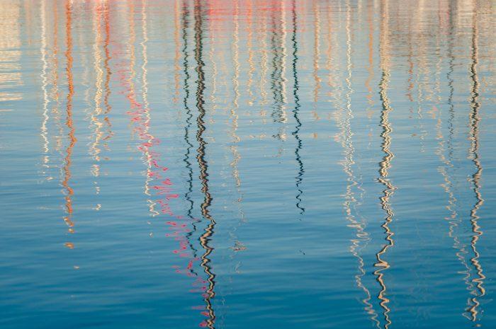 In de reflecties zie je de masten van zeilboten