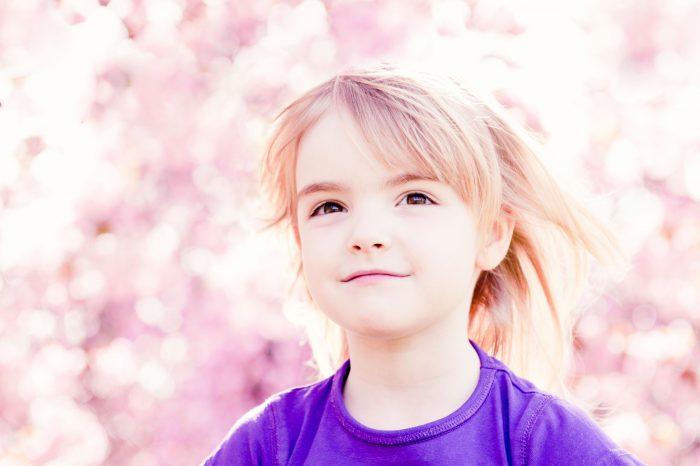 Het meisje zat op de schouders van haar vader. De bloesem vormde een mooie roze achtergrond.