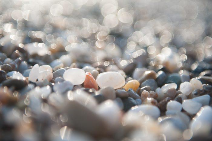 Er werd gefotografeerd met tegenlicht. Waterduppels op de kiezelsteentjes zorgen voor een mooi bokeh effect
