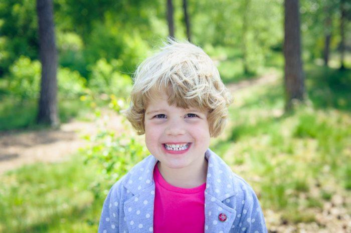 Het meisje op deze foto heeft een nepglimlach; ze laat haar tanden zien alsof ze naar de tandarts gaat