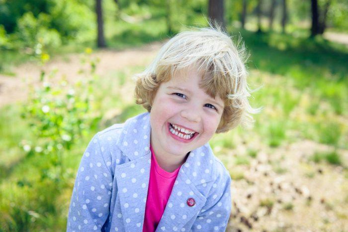 Het meisje op deze foto heeft een spontane glimlach, ze kijkt net niet naar de camera
