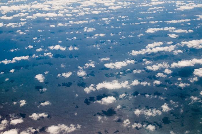 De wolken geven coole schaduwen op de zee