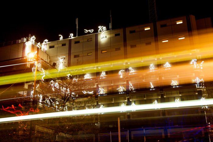 Door te fotograferen met een lange sluitertijd zijn meerdere poppetjes in beeld zichtbaar. De lichtstrepen van een voorbijrijdende bus maken de foto ook kleurrijker en dynamischer.