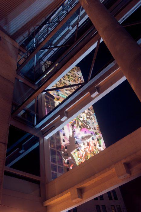 De projectie op het gebouw (de Admirant) schoof langzaam omhoog. Ik fotografeerde daarom een sluitertijd van 1/20s. Ik koos niet voor een standpunt waarbij het hele gebouw zichtbaar was, maar gebruikte een ander gebouw om de foto iets spannender te maken