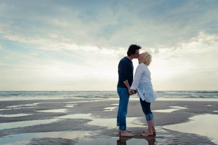 Stelletje op het strand dat elkaar een kus geeft