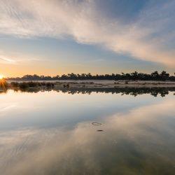 Bij deze zonsopkomst is de horizon heel bewust in het midden geplaatst. Door het fotograferen van de reflectie krijgt de foto een mooie symmetrische compositie.