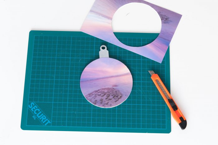 Houd het mesje niet te schuin langs het randje, anders snijdt je in de kerstbal zelf. Als je netjes werkt, kun je zo de ronde kerstbal eruit halen.