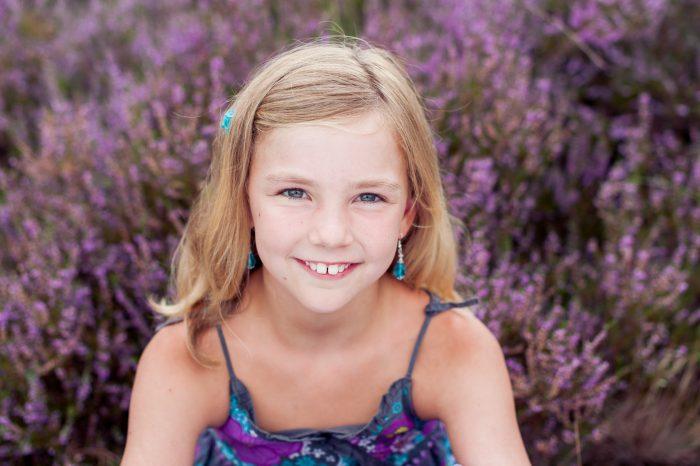 Bloeiende heide geeft een mooie paarse achtergrond bij portretfotografie en kinderfotografie