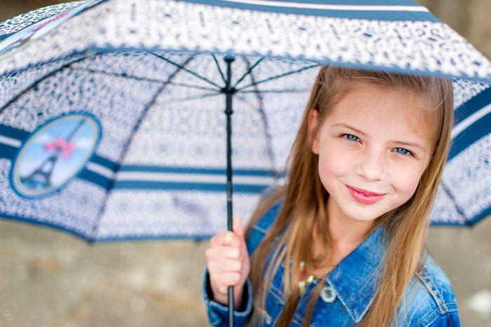 Door het grote diafragma is de voorkant van de paraplu en de achterkant alweer onscherp. De aandacht gaat daarom naar het gezicht van het meisje.