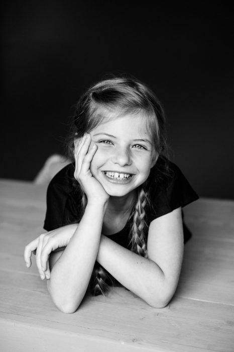 Het meisje lacht rechtstreeks naar de camera. Door de afstand zie je ook haar armen.