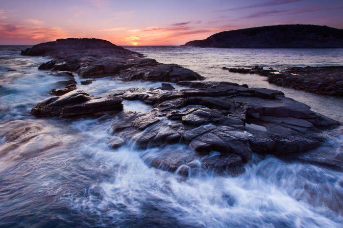 Het water dat tijdens op de rotsen slaat krijgt geeft de foto, vanwege de langere sluitertijd, een dynamisch effect.