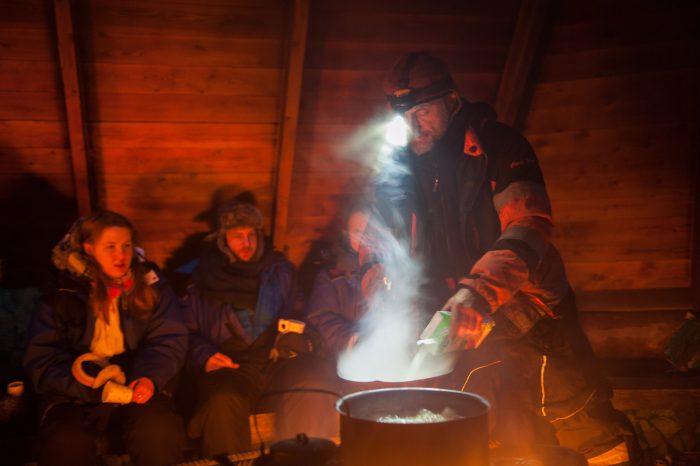 De finse gids maakt een soepje klaar op het kampvuur.