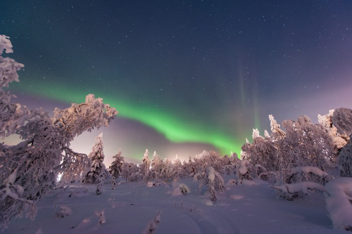 Noorderlicht fotograferen in een besneeuwd landschap met erboven een sterrenhemel.