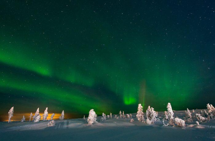 Noorderlicht fotograferen aan de top van de heuvel met erboven een sterrenhemel en in de verte licht van een andere stad.