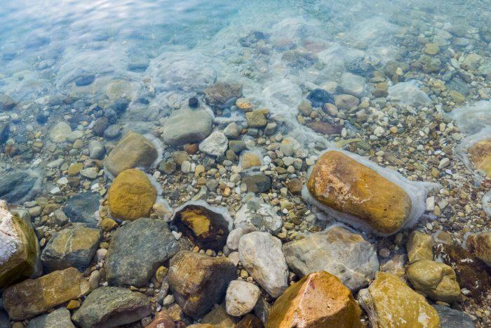 Je ziet de zoutlaag om de rotsen
