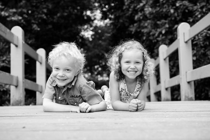 Twee kinderen poseren op een brug voor de foto