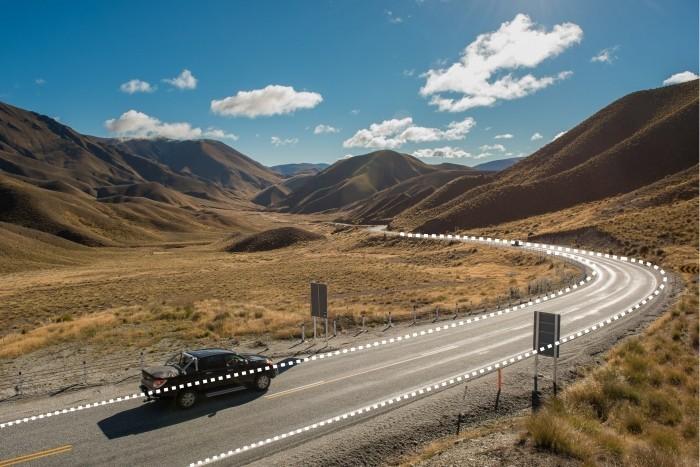 De weg vormt een leidende lijnen door de foto, de auto neemt je ook als het ware mee