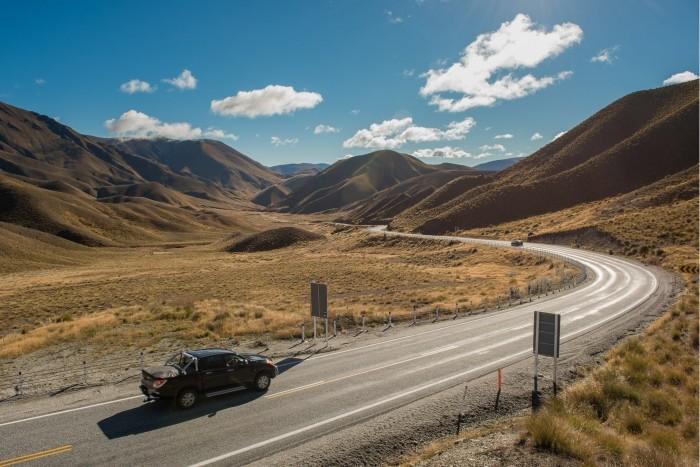 Auto rijdt over de Lindis Pass in Nieuw Zeeland
