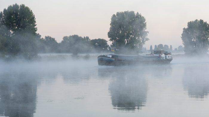 Schip vaart door de mist over de maas