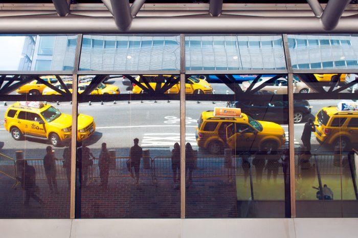 Door de ramen heeft deze foto drie lagen. Je ziet de buitenkant van het gebouw, de reflectie van de taxi's (en mijzelf 2x!) in het glas én je kijkt deels door het glas, waardoor je ook de mensen binnen ziet staan.