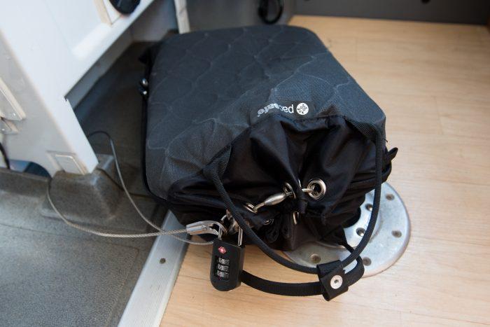 """In de 12L PacSafe passen ook twee 15"""" laptops. Hier had ik de tas bevestigd aan de voorstoelen van de kamper. Als we op pad gingen, legden we er natuurlijk iets overheen, zodat het niet opviel."""