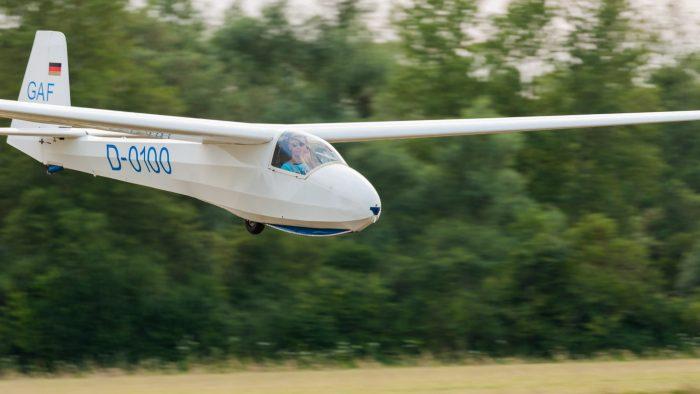Het vliegtuig is scherp, maar de achtergrond heeft duidelijk een zijwaartse bewegingsonscherpte door het panning.