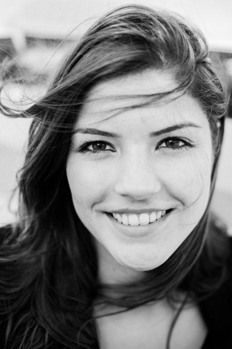 Kom je dichterbij, dan wordt een portret met oogcontact vaak iets intiemer. De wind door haar haren geeft de foto een speels effect.