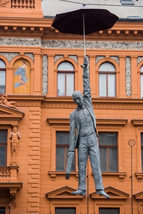 Het oranje van de achtergrond overheerst in de foto. Het grijze 'hangende' standbeeld valt amper op.
