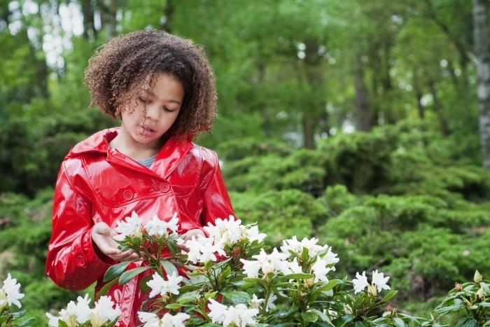 Meisje in rode regenjas kijkt naar witte bloem
