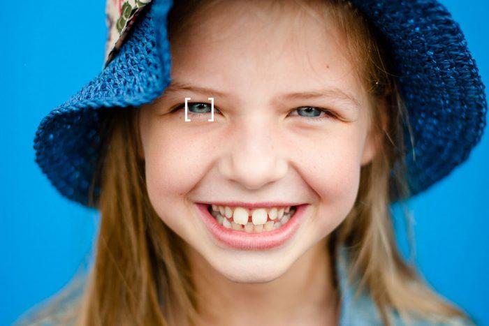 Deze portretfoto heeft weinig scherptediepte. Haar ogen zijn scherp, maar haren oren en het randje van de hoed zijn wazig.