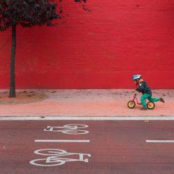 De combinatie van de iconen op het fietspad, de rode kleuren en het jongetje op de loopfiets, maakt deze foto helemaal af.
