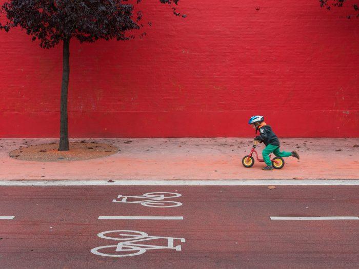 De combinatie van de iconen op het fietspad, de rode kleuren en het jongetje op de (rode) loopfiets, maakt deze foto helemaal af.